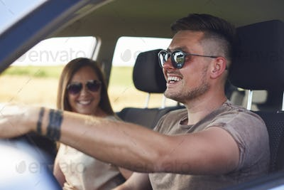 Young couple traveling by car in summertime