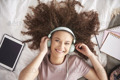 Beautiful teenage girl listening to music in her bed