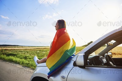 Young woman with rainbow flag enjoying the view