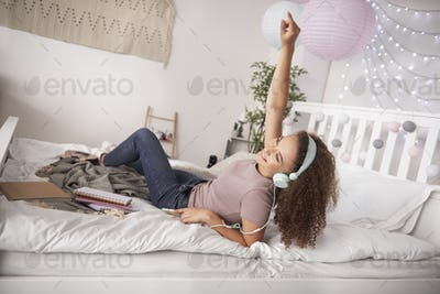 Happy teenage girl listening to music in her bed