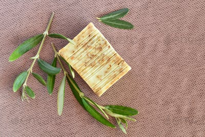 Handmade soap bars and olive branches on gunny background. Top view