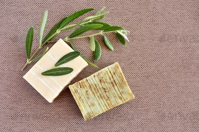 Handmade soap bars and olive branches on fabric background. Top view