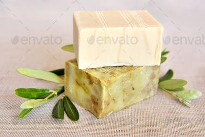 Handmade soap bars and olive branches on gunny background