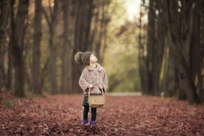 Adorable little girl with a basket in cold autumn day outdoors