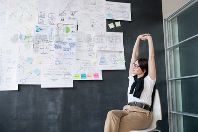 Young tired businesswoman stretching arms while sitting on chair by blackboard