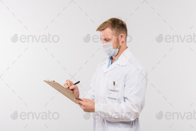 Young doctor in whitecoat and protective mask making prescriptions for patient