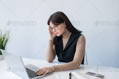 Young serious businesswoman touching head while concentrating on work
