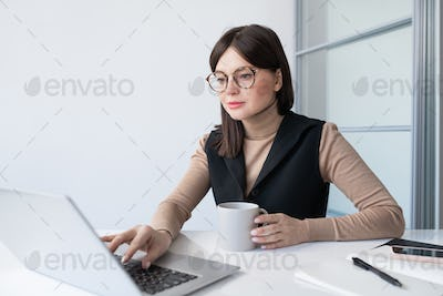 Young contemporary businesswoman with drink analyzing online financial data