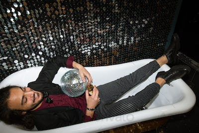 Cheerful young well-dressed man with flute of champagne relaxing in bathtub