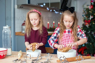 Little happy girls baking gingerbread cookies for Christmas at home kitchen