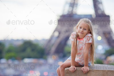 Adorable little girl background the Eiffel tower during summer vacation in Paris