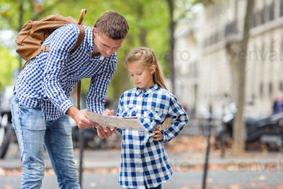 Adorable little girl and father with map of european city outdoors