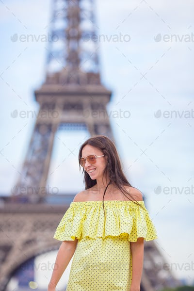 Happy woman in Paris background the Eiffel tower during summer vacation