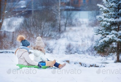 Little adorable girls enjoy a sleigh ride. Child sledding. Children play outdoors in snow. Family