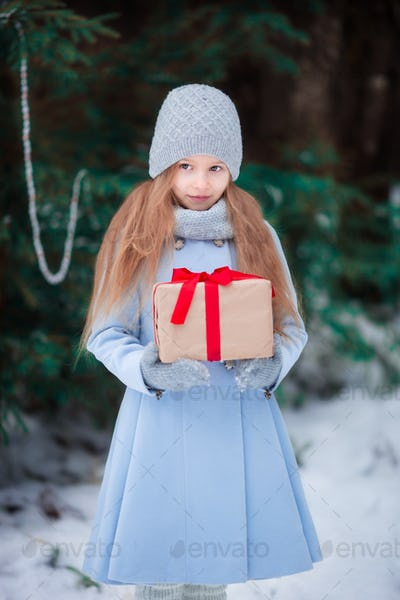 Little girl with christmas box gift in winter outdoors