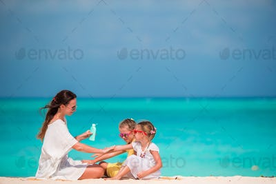 Young mother applying sunscreen on her kids