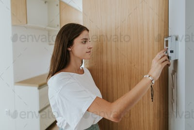 Portrait of young woman adjusting thermostat in new apartment.