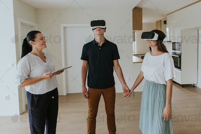 Estate agent with young couple wearing VR headsets in new apartment.