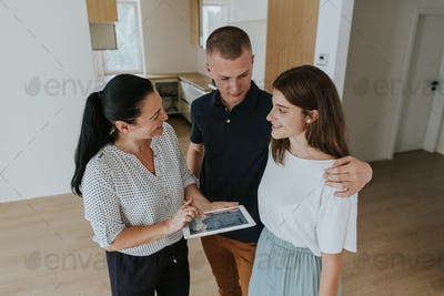Estate agent with digital tablet showing young couple new apartment.