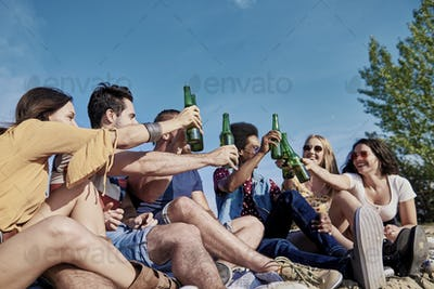 Group of young people making a toast outdoors