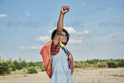 African man with rainbow flag outdoors