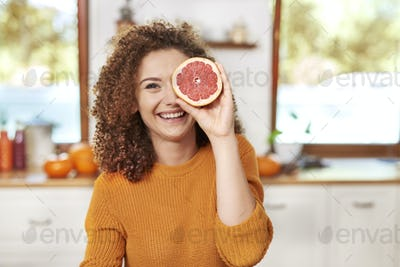 Portrait of  beautiful woman having fun with fruit in kitchen