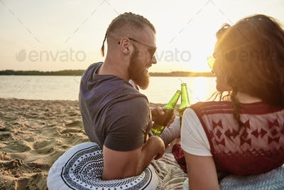Rear view of young couple drinking beer on the beach