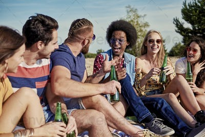 Six young people drinking beer outside