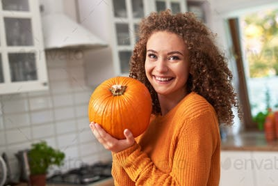 Portrait of beautiful woman holding a  pumpkin