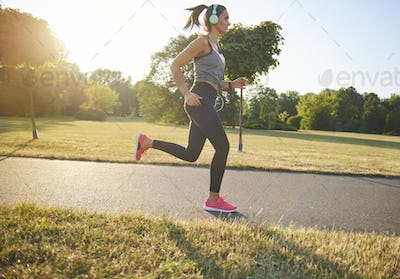Side view of young woman running and listening to music