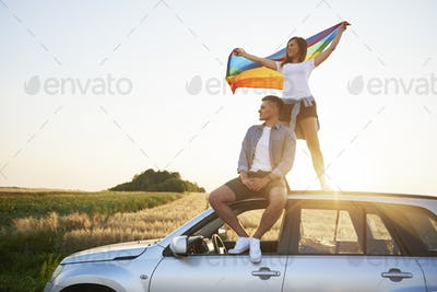 Young couple with rainbow flag enjoying the view