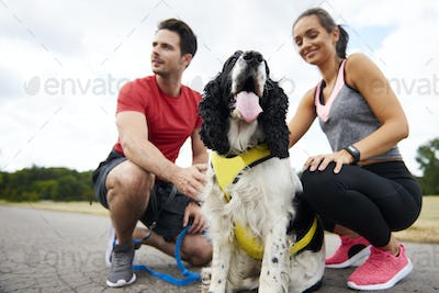 Young  couple and dog after workout on the fresh air