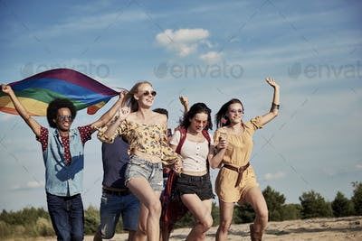 Happy friends with rainbow flag running outdoors