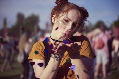Girl blowing some confetti pieces