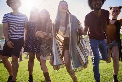 Group of happy people running at the music festival