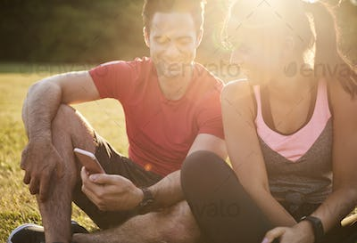 Happy couple using mobile phone after hard workout
