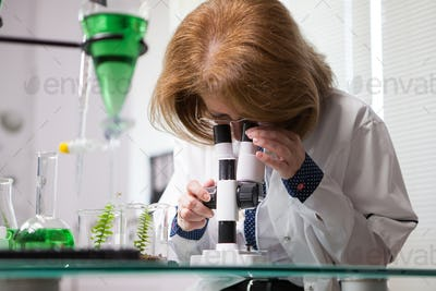 Female in microbiological industry adjusting her microscope