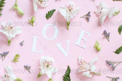 Flowers nad word LOVE on a light pink background