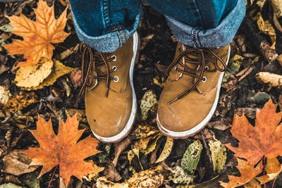 Boots against the background of dry leaves in the forest