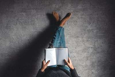 Girl reads a book with his legs to the wall, gray background, education, hobby, development