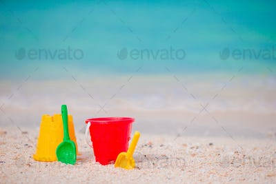 Kid's beach toys on white sand. Buckets and blades for kids on the white sandy beach after