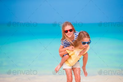 Adorable little caucasian girls at beach during summer vacation. Happy kids having fun together on