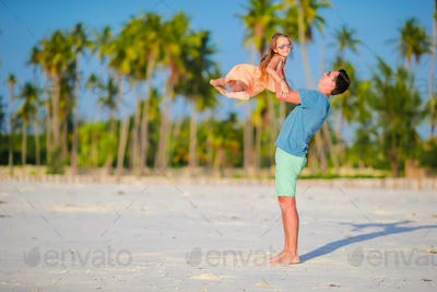 Happy father and his adorable little daughter at tropical beach. Caucasian family having fun