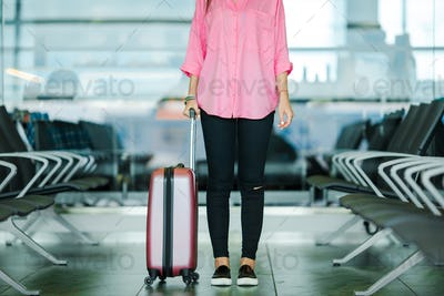 Closeup airplane passenger and pink baggage in an airport lounge waiting for flight aircraft. Young