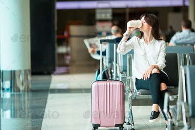 Airline passenger in an airport lounge drinking coffee and waiting for flight aircraft. Caucasian