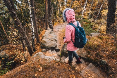 Adult women with backpack on hiking trail in forest. Travel lifestyle adventure concept