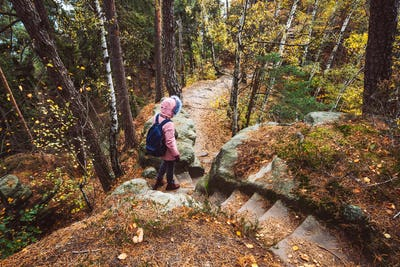 Adult women with backpack on hiking path trail in forest. Travel lifestyle adventure concept