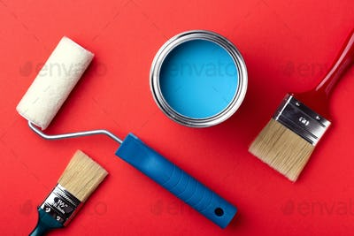 Can of Blue Paint with Brushes and Paint Roller on Red Background.