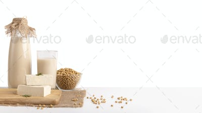 Soy milk, beans and tofu cheese on white background