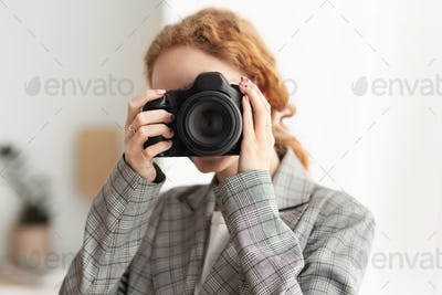 Successful photographer taking photo with professional camera